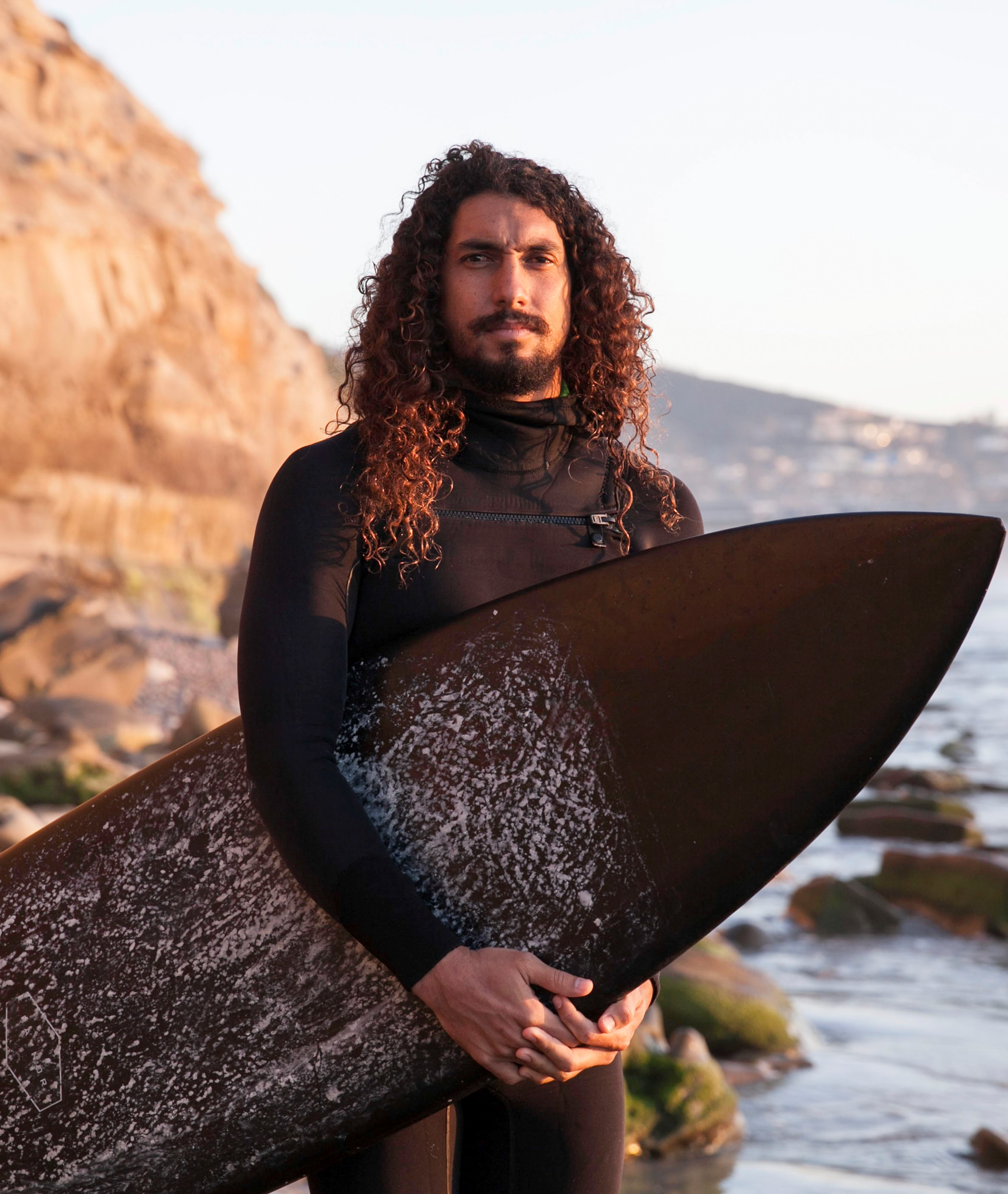 Cliff Kapono standing with surf board